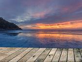 Sunset over sea the Beach with Wood floor — Stock Photo
