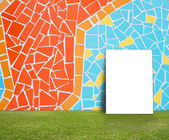Blank Poster with Colorful mosaic tile wall and green lawn for information message — Stock Photo