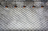Lamp with wired fence and Grungy concrete wall — Stock Photo