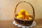 Orange model in basket on wooden table — Stock Photo