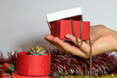 Female hand is holding a red and white paper Christmas present box which is opened and contains a necklet and bracer — Stock Photo
