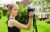 Teenager girl while photographing in the garden — Stock Photo