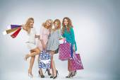 Four charming ladies with plenty shopping bags — Stock Photo