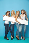 Portrait of four girlfriends holding a board — Stockfoto