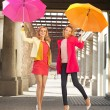 Two cheerful girlfriends jumping with umbrellas — Stock Photo #60098817