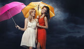 Two joyous young women with colorful umbrellas — Stock Photo
