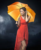 Delighted brunette lady with orange umbrella — Stockfoto