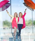 Two blonde ladies having fun with colorful umbrellas — Stockfoto