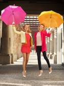 Blonde jumping women with colorful umbrellas — Stock Photo