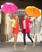 Two cheerful girlfriends jumping with umbrellas — Stock Photo
