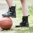 Girl holding a basket ball under her boot — Fotografia Stock  #76494315