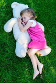 Sad little girl lying on grass with large teddy bear — Stock Photo