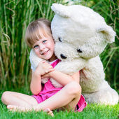 Little cute girl sitting in the grass with large teddy bear — Stock Photo