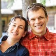 Cheerful couple sitting in front of a new house — Stock Photo #62971203