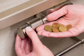 Radiator thermostat, coins and hand — Stock Photo
