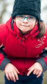 Portrait of a little girl in a black cap and blue eyeglasses on  — Stock Photo