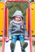 Serious girl girl on children chute ready to slide — Stock Photo