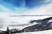 Winter landscape, snowy mountain peaks and low clouds — Stock Photo