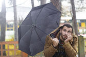 Young man with umbrella wondering — Stock Photo