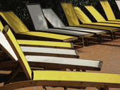 Line of yellow and white sun loungers — Stock Photo