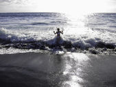 Enjoying the waves hitting the volcanic beach — Stock Photo