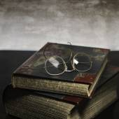 Two old books with antique reading glasses on grey — Stock Photo