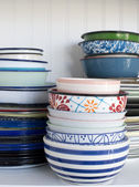 Pile of old dishes on a white shelf — Stock Photo