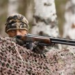 Hunter aiming from behind camouflage netting — Stock Photo #58401969