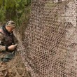 Hunter and camouflage netting — Stock Photo #58401975