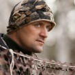 The hunter looks out from behind camouflage netting — Stock Photo #58402001