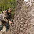 Hunter pulls camouflage netting — Stock Photo #58402033