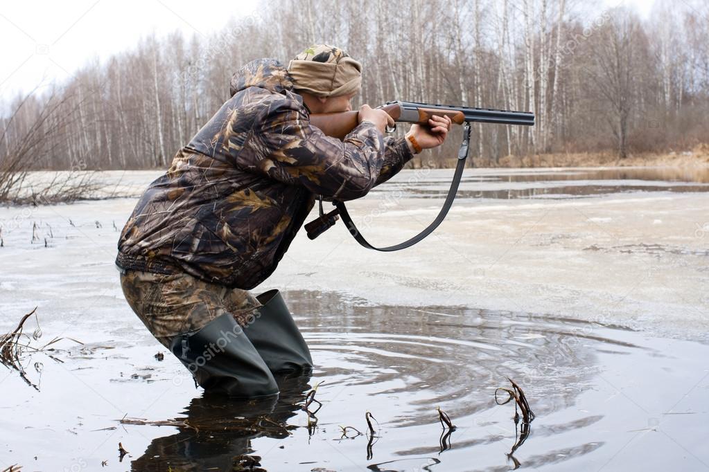 охотник стреляет из ружья с движущейся лодки по направлению движения