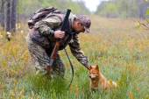 Hunter stroking the dog — Stock Photo