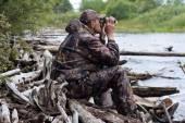 Sitting hunter  looks through the binoculars on the river — 图库照片