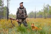 Caçador com uma arma e um cachorro num pântano — Fotografia Stock