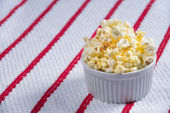 Closeup of a Ramekin Full of Popcorn on a white and red background — Stock Photo
