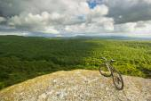 Bicycle on a cliff with covered by forest hills — Stock Photo