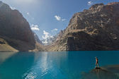 Standing on a blue lake shore in the mountains — Stok fotoğraf