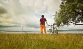 Man with bicycle on a bank of blue lake — Stock Photo