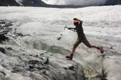 Jumping girl across the ice  crack in glacier — Stock Photo