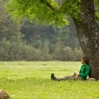Man sitting under big tree on a green meadow — Stock Photo #67313859