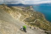 Rock climber climbs mountain with sea on background — Stock Photo