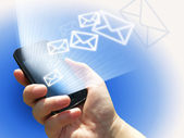 Electronical communication - sending e-mails from mobile phone — Stock Photo