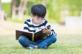 Little asian boy write homework in the garden — Foto Stock