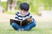 Little asian boy write homework in the garden — Stock Photo