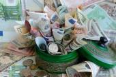 A lot of money in green moneybox — Stock Photo