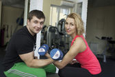 Fitness couple are holding a dumbbells — Stock Photo