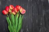 Czerwone tulipany na prosty drewniany stół. Widok z góry z kopii przestrzeni — Zdjęcie stockowe
