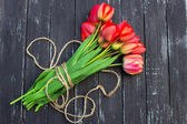 Red tulips on rustic wooden table. Top view with copy space — Stock Photo