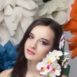 Beauty portrait of a model with a wreath of flowers on her head, holding a bouquet of roses and beautiful makeup — Stock Photo #77089979